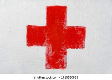 Red cross painted by hand on white wall. First aid kit medical icon. Medicine health hospital sign or emergency medicine symbol, health care.