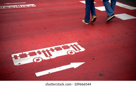 Red crosswalk with bus and traffic direction signs