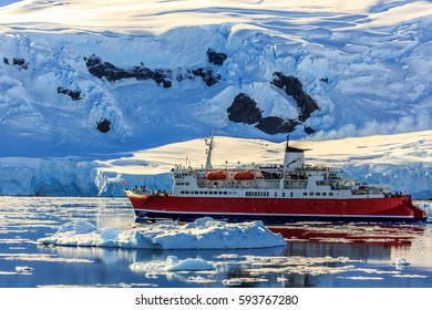 Red cruise steamboat among the icebergs with glacier in background, Neco bay, Antarctica