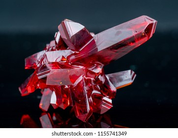 red crystal of natural origin. close up of crystal in ruby color on black background