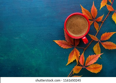 Red cup of black coffee and branch of colorful autumn leaves  (Virginia creeper)  on a dark blue-green wooden table.  Flat lay