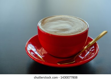 Red cup of cappuccino coffee on black table