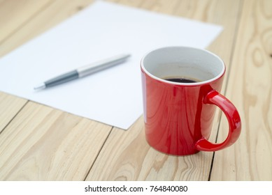 Red cup of coffee with blank white paper and pen on the wooden desk.