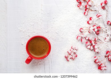 Red cup of coffee and branches with hawthorn berries on an old white wooden background. Flat lay.