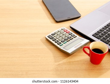 Red cup coffee and calculator and labtop and tablet on wood table backgrounds