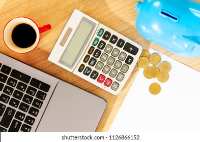 Red cup coffee and calculator, labtop and piggy bank with money coin on paper blank pages backgrounds above, Top views
