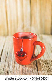 a red cup of coffee with Christmas ornament on the old wooden panel background.
