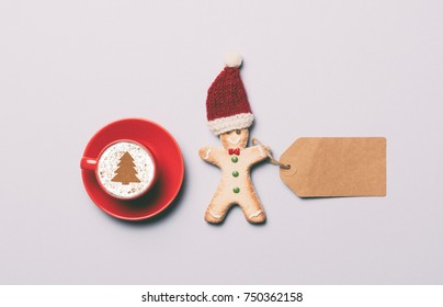 Red cup of coffee and Gingerbread man with paper tag on grey background, view above