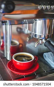 A red cup of coffee with coffee maker machine