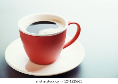 Red cup of coffee and saucer