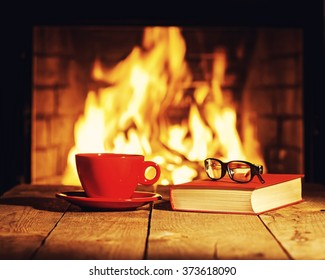 Red cup of coffee or tea, glasses and old book on wooden table near fireplace. Winter and Christmas holiday concept. Photo with retro filter effect.
