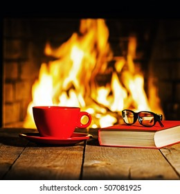 Red cup of coffee or tea, glasses and old book on wooden table near fireplace. Winter and Christmas holiday concept.