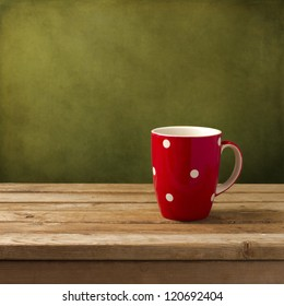 Red cup with dots on wooden table over grunge green background