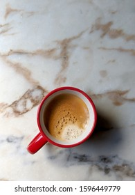 Red cup of expresso coffee on a marble surface