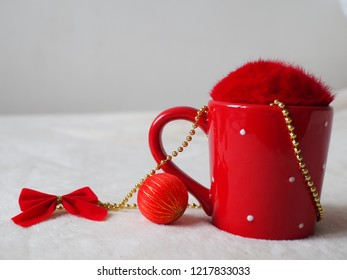 Red cup with fluffy cover, bauble and bow. Close up