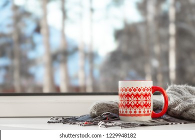 Red cup of hot drink on the window sill, with winter landscape in snow. Cozy home, winter weekend and holidays, Christmas morning concept.