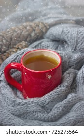 Red cup of hot tea with pine cones and scarf decoration