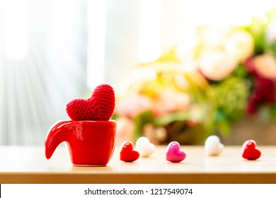 Red cup for keep a red heart with love put in the desk on flower background in the home, for supporting when people get who lack of desire with love concept.