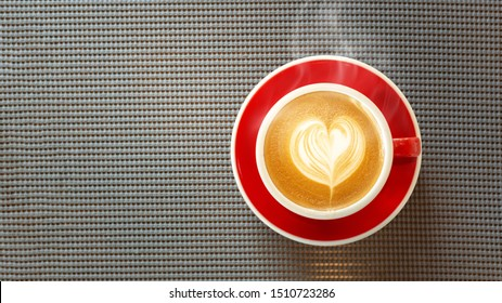 Red cup, Latte coffee heart shaped on wooden tablecloth