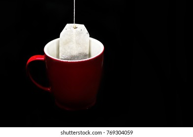Red cup, mug of tea on black with copy space. Blank, red mug. herbal infusion etc also.