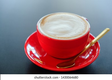 Red cup cappuccino​ coffee​ on black table