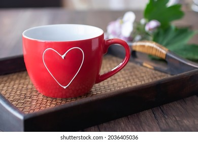 Red cup on a brown tray on a brown wooden table. Soft focus.
