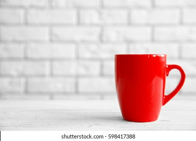 Red cup on table against white brick wall background