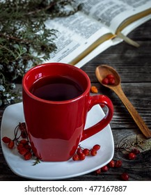 Red Cup on wooden background with wooden spoon and book