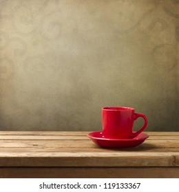 Red cup on wooden table over grunge background