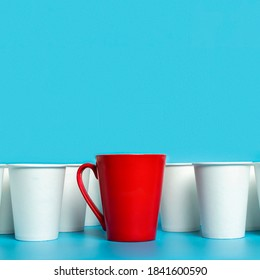Red cup surrounded by white paper cups on a blue background. Concept boss, unique, friendly team. Copy space