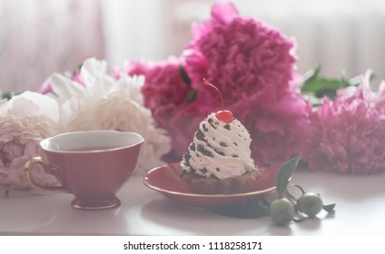 a red cup of tea and a big creamy white cake with cherry and chocolate on a red plate and pink and white peones