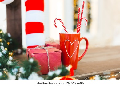 Red cup of tea or coffee or hot chokolate with sweets and gift - Christmas Holiday Background