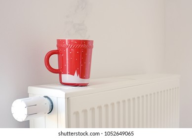 Red cup of tea on the heating radiator