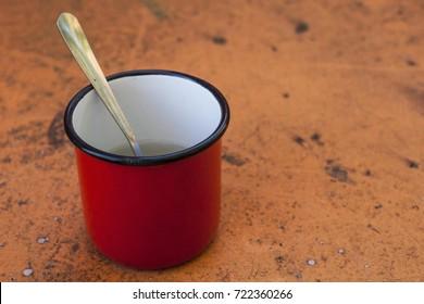 Red cup of tea on an orange background. Tin coated enamel mug.