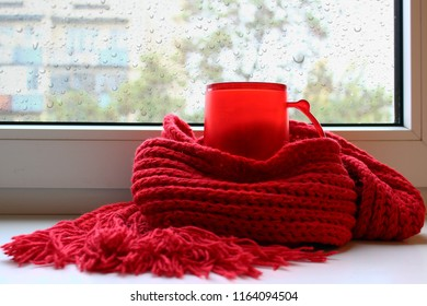 Red cup of tea on the window still. Warm knitted red scarf. Rainy day. Big raindrops on window.
