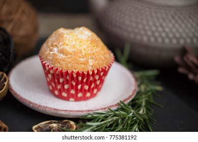 red cupcake in a rew paper on a plate on a dark smoke background with rosmary branch and dried lemon and flowers/ home winter atmosphere