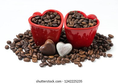 red cups with coffee beans and chocolate candies in the form of heart, top view