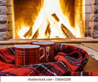 Red  cups  for  hot tea and cozy  warm scarf near  fireplace, in country house, winter vacation, horizontal.