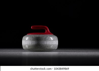 Red curling stone on ice isolated on the black background. curling sport. close-up