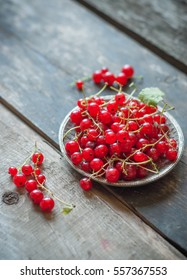 red currant berries in a metal dish on a rustic wooden background. close up and selective focus