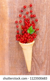 Red currant fruits in an ice cream cone on wooden table. Focus on leaf.