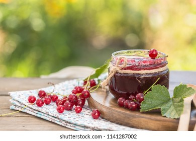 Red currant jam in a jar on a natural background. Tasty food.