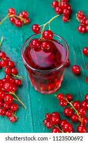 Red currant juice in glass with fruits on wood table. Focus on redcurrant in glass.