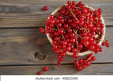 Red currant on brown wooden table