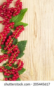 Red currants and green leaves on wooden background