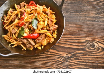 Red curry Bamboo Shoot Stir Fried with beef in wok and wooden background.
