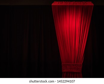 red curtain against black wall at theater