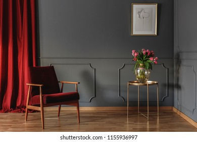 Red curtain and burgundy armchair standing in grey room interior with pink tulips on gold end table and simple poster hanging on the wall with wainscoting