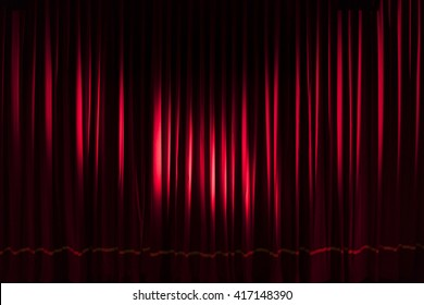 Red curtain closed and illuminated by two spotlights from left and right - concept theater show music entertainment performance background stage lockdown Covid-19 shutdown empty dramatic texture