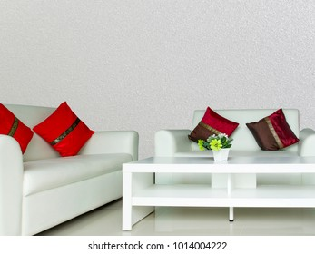 red cushions on white sofa in living room with white concrete wall